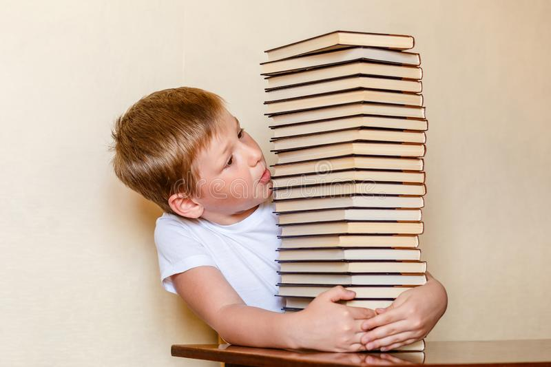 An eight-year-old child looks at a large stack of books. people and books. Learning to read stock photos