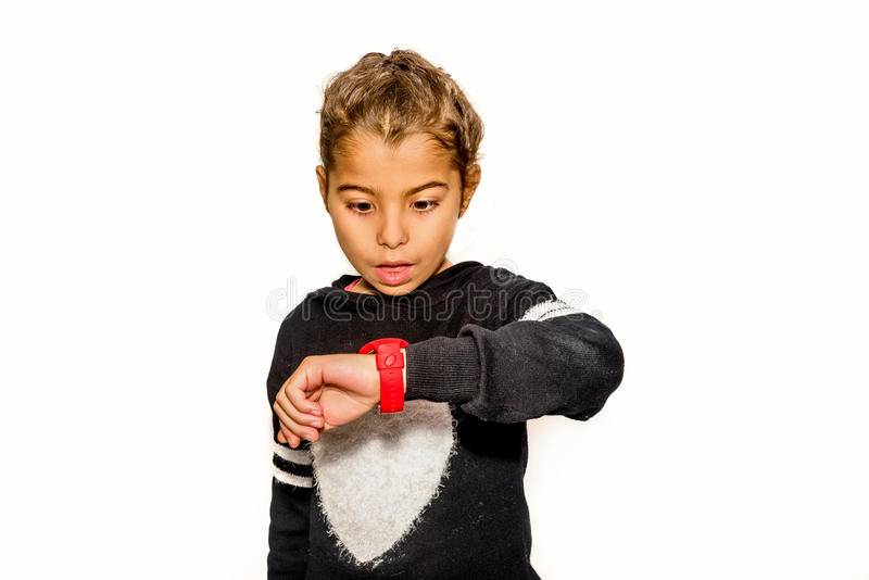 Eight year old girl looking at her watch surprised at what time royalty free stock images