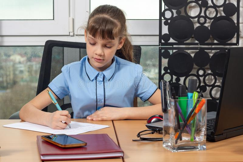 An eight-year-old girl at an office table is writing an important document. An eight-year-old girl at an office table is writing an important  document royalty free stock photography