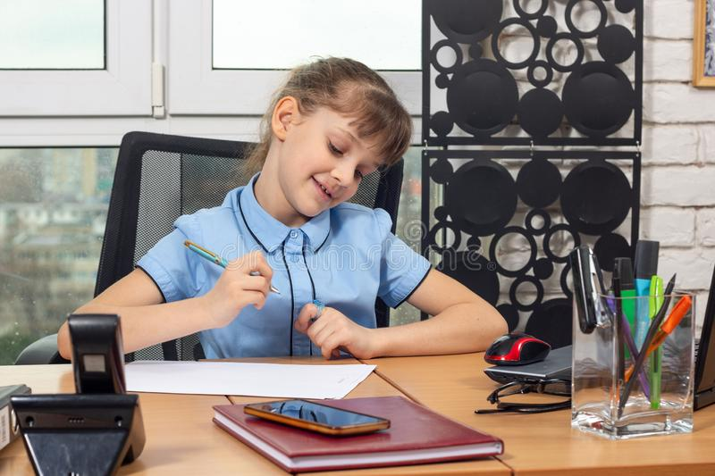 Eight-year-old girl rejoices after signing another document. Eight-year-old girl rejoices after signing  another document royalty free stock photography