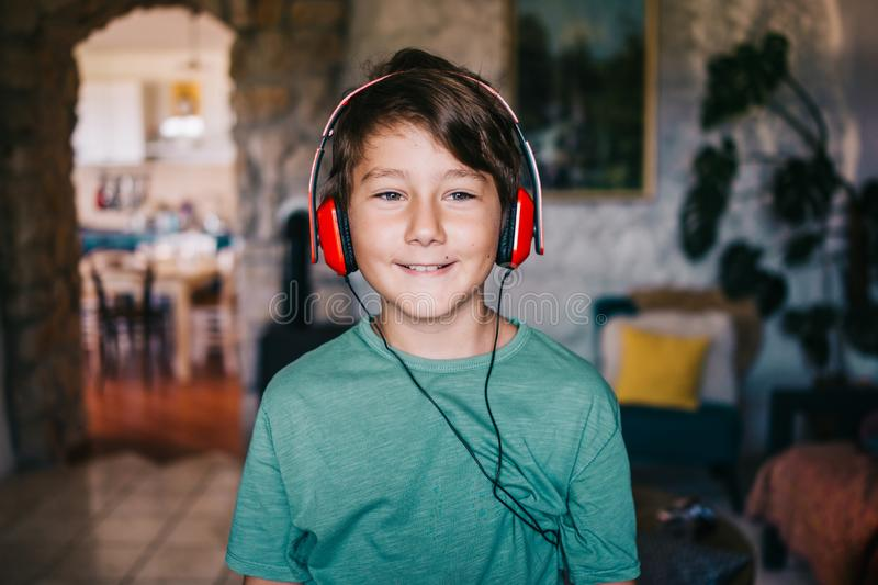 Eight years old boy listening music stock photos