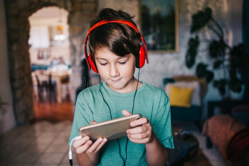 Eight years old boy listening music on mobile phone royalty free stock photography