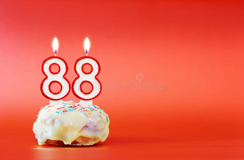Eighty eight years birthday. Cupcake with white burning candle in the form of number 88. Vivid red background with copy space royalty free stock images