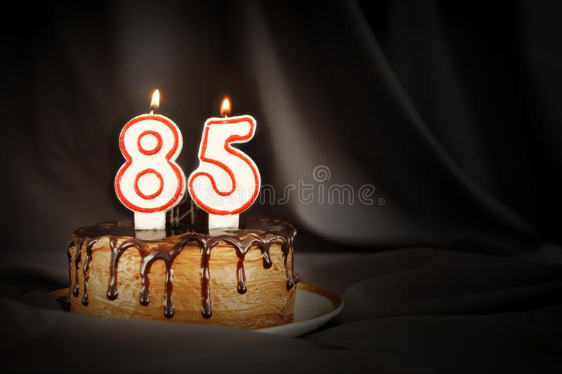Eighty five years anniversary. Birthday chocolate cake with white burning candles in the form of number Eighty five. Dark background with black cloth royalty free stock images