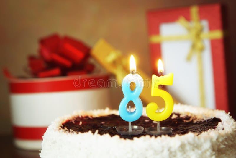 Eighty five years birthday. Cake with burning candles and gifts. Eighty five years birthday. Sweet cake with burning candles and gifts stock images