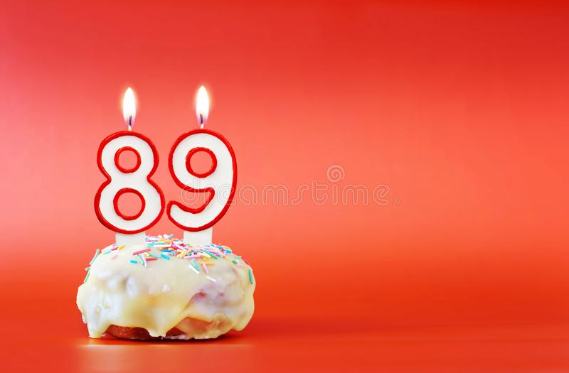 Eighty nine years birthday. Cupcake with white burning candle in the form of number 89. Vivid red background with copy space stock images