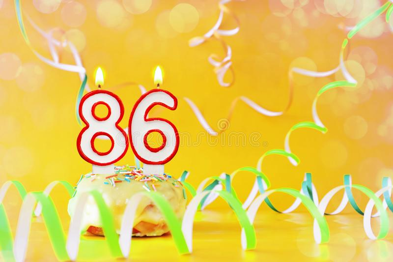 Eighty six years birthday. Cupcake with burning candles in the form of number 86. Bright yellow background with copy space stock images
