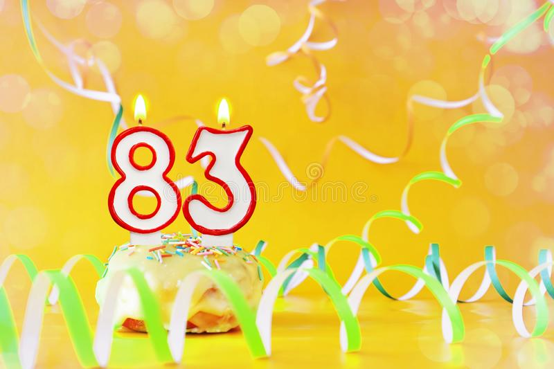 Eighty three years birthday. Cupcake with burning candles in the form of number 83. Bright yellow background with copy space stock photography