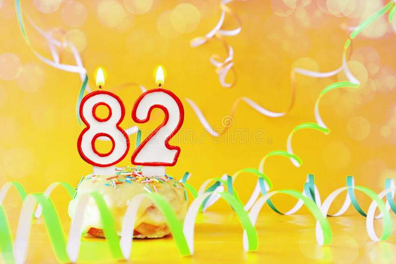 Eighty two years birthday. Cupcake with burning candles in the form of number 82. Bright yellow background with copy space royalty free stock photo