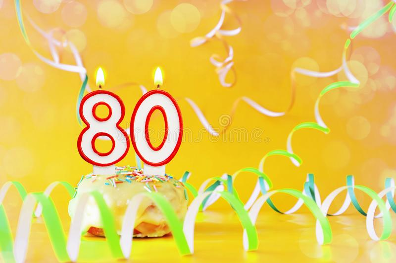 Eighty years birthday. Cupcake with burning candles in the form of number 80. Bright yellow background with copy space stock photography