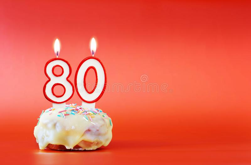 Eighty years birthday. Cupcake with white burning candle in the form of number 80. Vivid red background with copy space stock photos