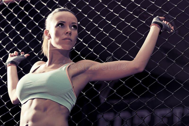Eignung der jungen Frau in kickboxing Trainingskäfig lizenzfreie stockbilder