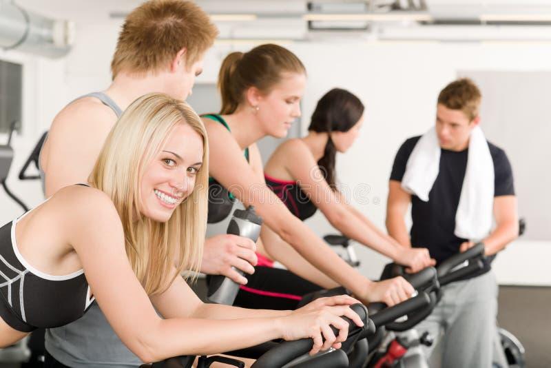 Eignung-Gruppe von Personen auf Gymnastikfahrrad stockbild
