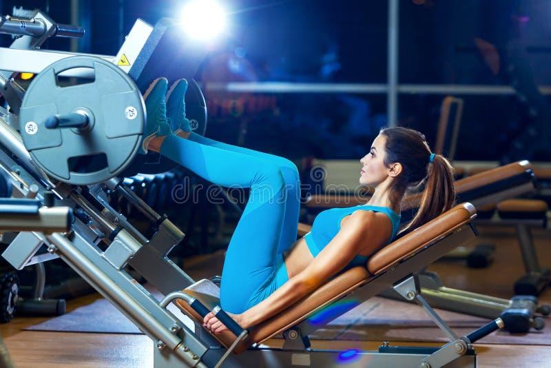 Eignung, Sport, Bodybuilding, Trainieren und Leutekonzept - junge Frau, die Muskeln auf Beinpressemaschine in der Turnhalle biegt lizenzfreies stockbild
