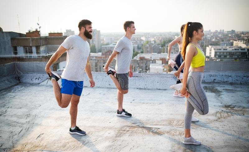 Eignung, Sport, Freundschaft und gesundes Lebensstilkonzept Gruppe des Trainierens der gl?cklichen Menschen lizenzfreie stockfotografie