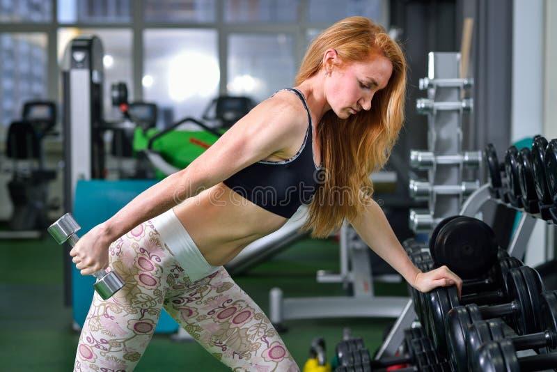 Eignung, Sport, Lebensstil ausübend - die attraktive junge Frau, die Gewichtheben tut, trainiert an der Turnhalle lizenzfreies stockbild