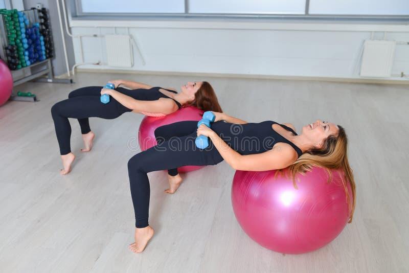 Eignung, Sport, Lebensstil ausübend - Frauengruppe, die Übungen mit Dummköpfen und Sitz ballsin eine Pilates-Klasse an tut lizenzfreies stockfoto
