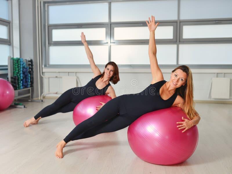Eignung, Sport, Lebensstil ausübend - Frauengruppe, die Übungen mit Sitzbällen in einer Pilates-Klasse an der Turnhalle tut lizenzfreies stockfoto