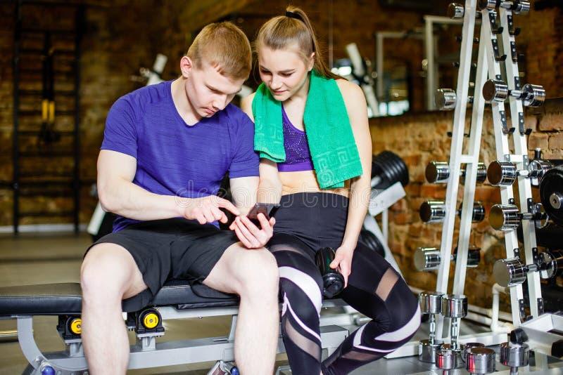 Eignung, Sport, Technologie und Abnehmenkonzept - Frau und persönlicher Trainer mit Smartphone- und Wasserflaschen in der Turnhal stockfotografie