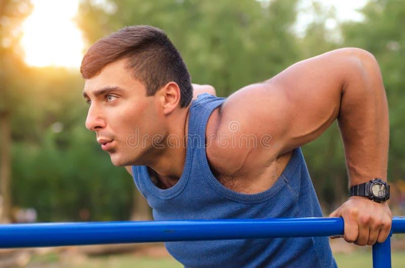 Eignung, Sport, trainierend, Ausbildungs- und Lebensstilkonzept - der junge Mann, der Trizeps tut, tauchen auf Barren draußen ein stockbild