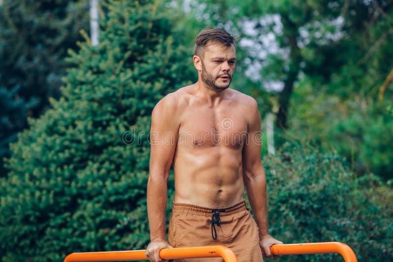 Eignung, Sport, trainierend, Ausbildungs- und Lebensstilkonzept - der junge Mann, der Trizeps tut, tauchen auf Barren draußen ein stockfotos