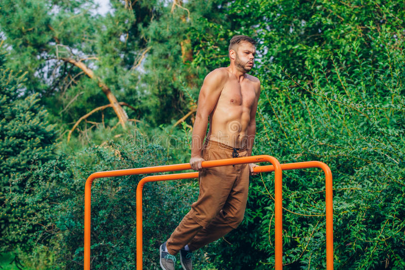 Eignung, Sport, trainierend, Ausbildungs- und Lebensstilkonzept - der junge Mann, der Trizeps tut, tauchen auf Barren draußen ein lizenzfreie stockfotografie