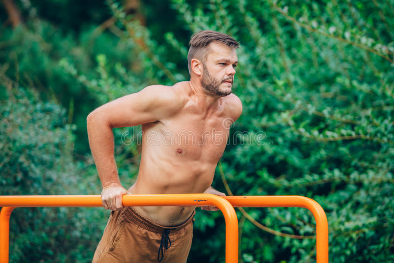 Eignung, Sport, trainierend, Ausbildungs- und Lebensstilkonzept - der junge Mann, der Trizeps tut, tauchen auf Barren draußen ein stockfoto