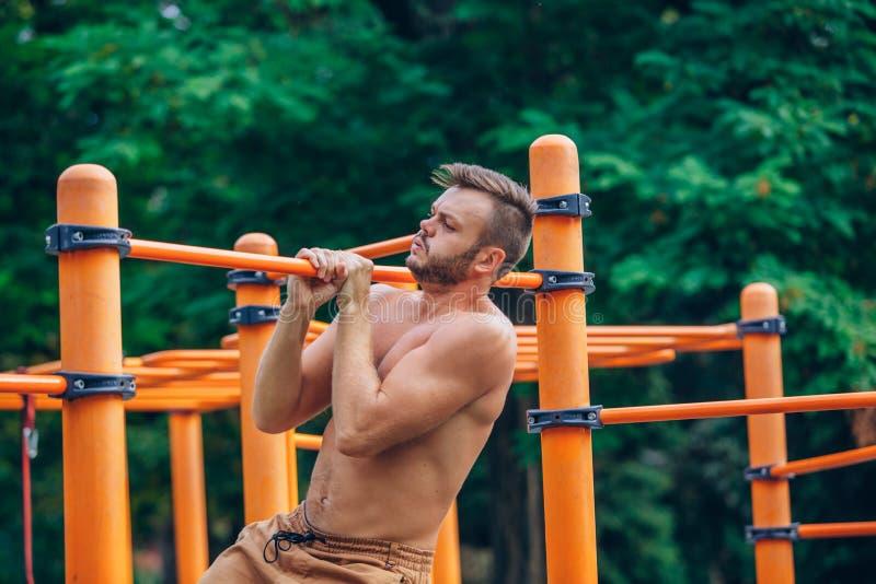 Eignung, Sport, trainierend, Ausbildungs- und Lebensstilkonzept - der junge Mann, der Zug tut, ups auf horizontale Stange draußen lizenzfreies stockbild