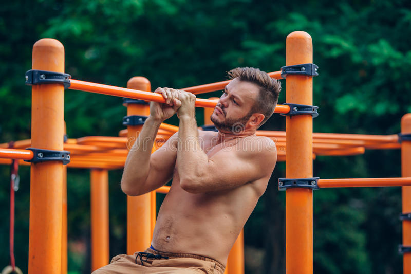 Eignung, Sport, trainierend, Ausbildungs- und Lebensstilkonzept - der junge Mann, der Zug tut, ups auf horizontale Stange draußen stockbild