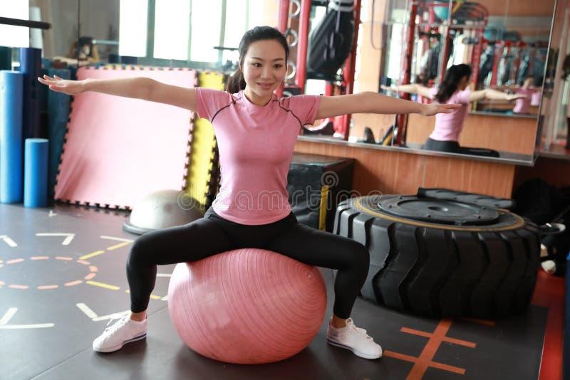 Eignung, Sport, Training, Turnhalle und Lebensstilkonzept - junge Frau, die Übung auf Eignungsball tut Ausrüstung, meditieren lizenzfreie stockfotografie