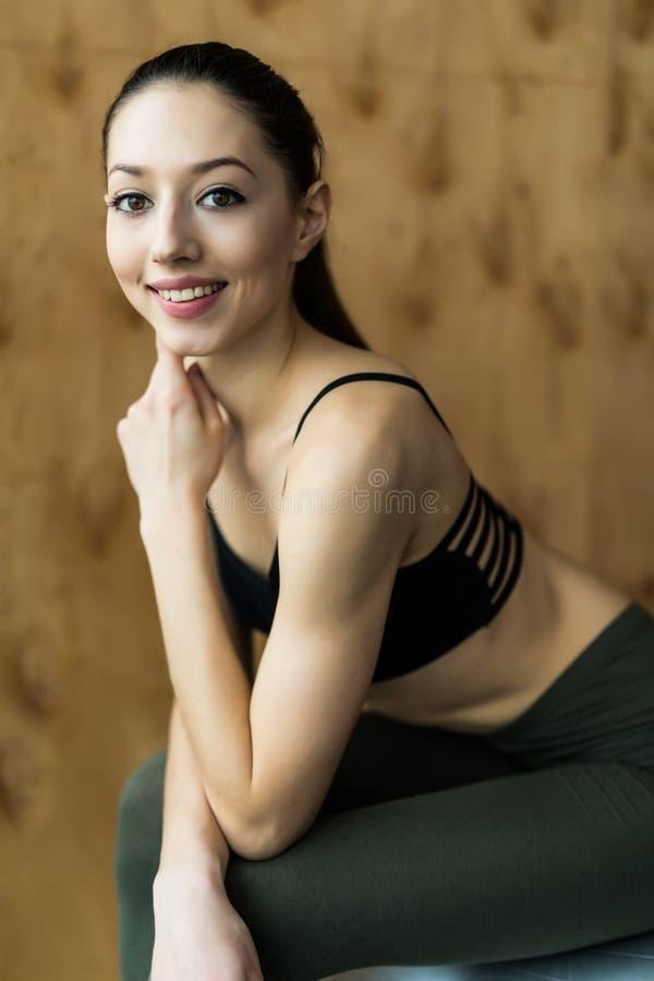 Eignung, Sport, Training, Turnhalle und Lebensstilkonzept - junge Frau, die auf Übungseignungsball sitzt lizenzfreie stockfotografie