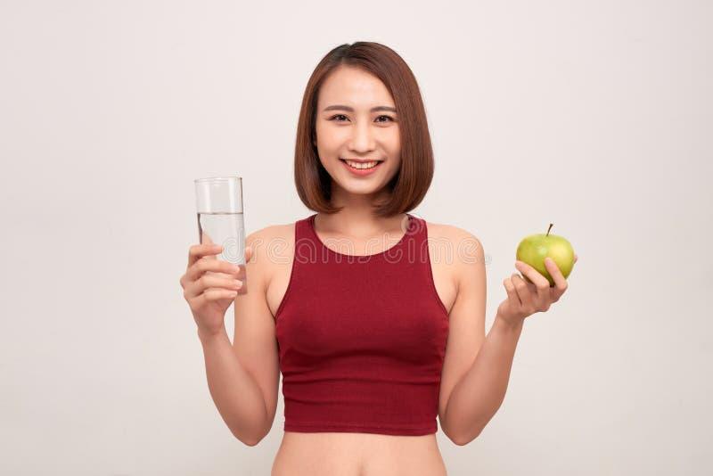 Eignungfrau, die tragendes messendes Band des Apfels isst Passende sportliche multikulturelle asiatische/kaukasische weibliche Ei stockfotos