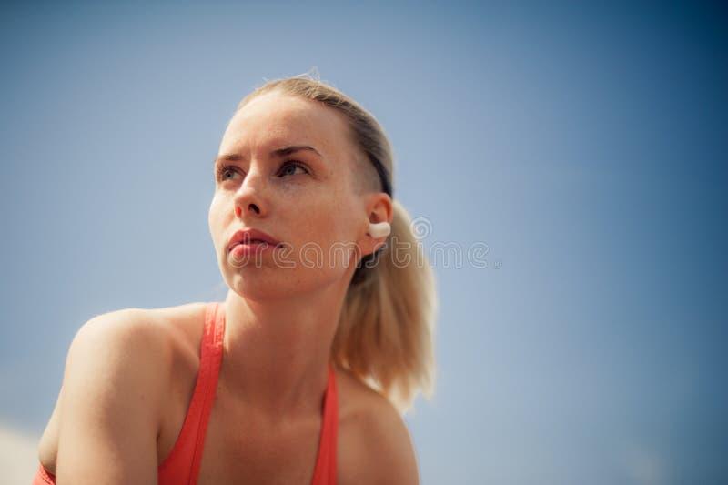 Eignungs-Frauen-hörende Musik in den drahtlosen Kopfhörern, Trainings-Übungen auf Straße tuend Sportart Bluetooth-Kopfhörer lizenzfreie stockfotos