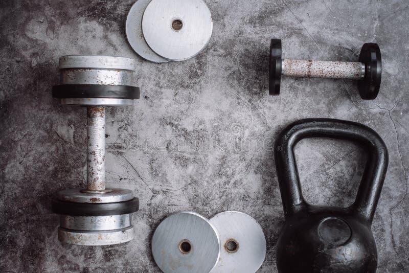 Eignungs- oder Bodybuildingkonzepthintergrund Alte Eisen Dummköpfe und Kettlebell auf Grau, conrete Boden in der Turnhalle lizenzfreies stockfoto