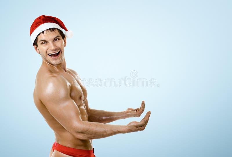 Eignungs-sexy Santa Claus-Griff und -lächeln, auf blauem Hintergrund lizenzfreie stockfotos