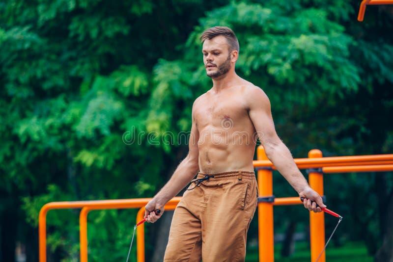 Eignungs-, Sport-, Trainings- und Lebensstilkonzept - bloß-chested Springen des gesunden Athleten mit dem Springseil im Freien stockfotografie