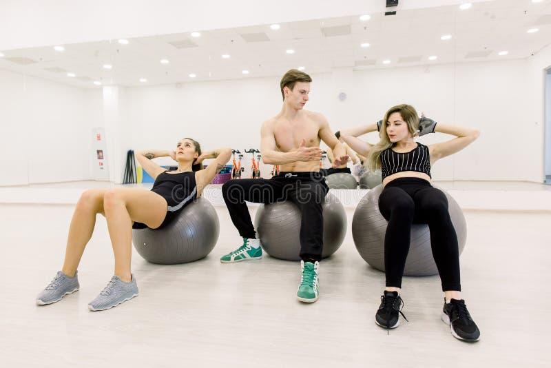 Eignungs-, Sport-, Trainings- und Lebensstilkonzept - Gruppe von Personen, die Bauchmuskeln auf fitball in der Turnhalle biegt stockbild