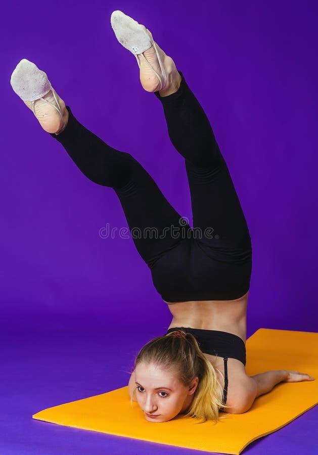 Eignungs-, Sport-, Trainings- und Lebensstilkonzept - lächelnde Frau, die Übungen auf Matte in der Turnhalle tut stockbild