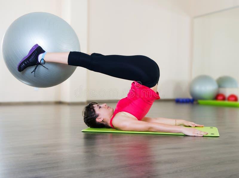 Eignungs-Training der jungen Frau in der Turnhalle mit fitball stockbilder