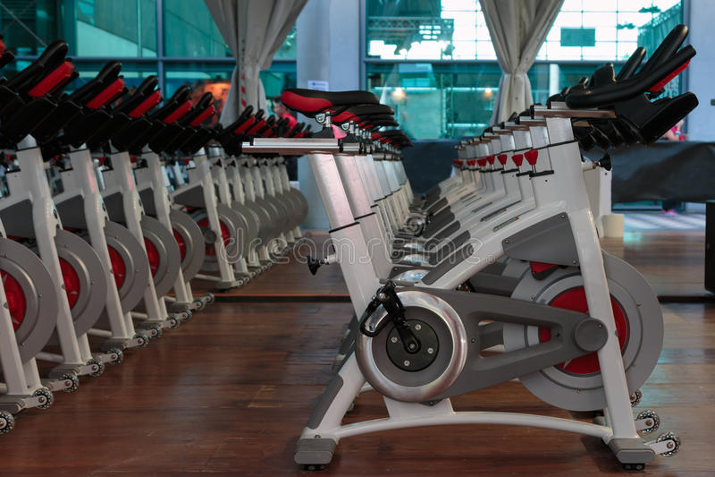 Eignungs-Training in der Turnhalle: Gruppe moderne spinnende Fahrräder in der Linie lizenzfreie stockfotografie