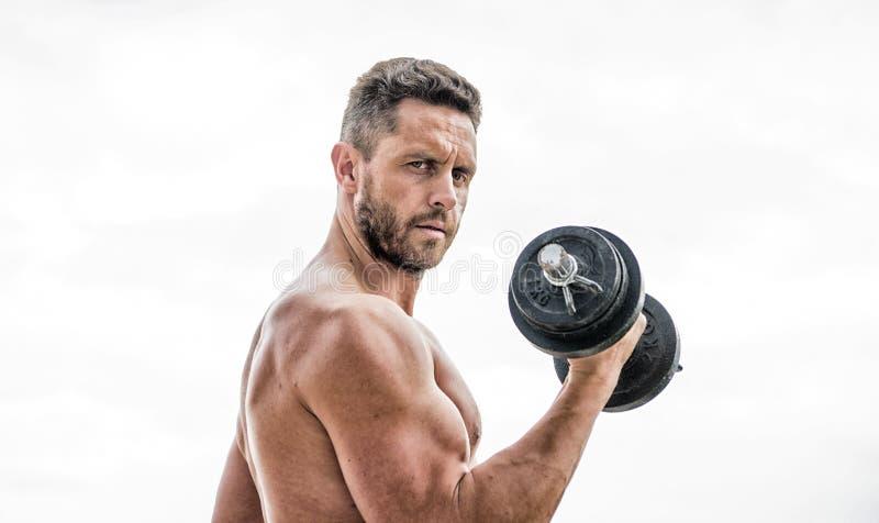 Eignungs- und Bodybuildingsport Turnhallentrainingskonzept Dummkopf?bungsturnhalle Muskul?ser Mann, der mit Dumbbell trainiert pr stockbild