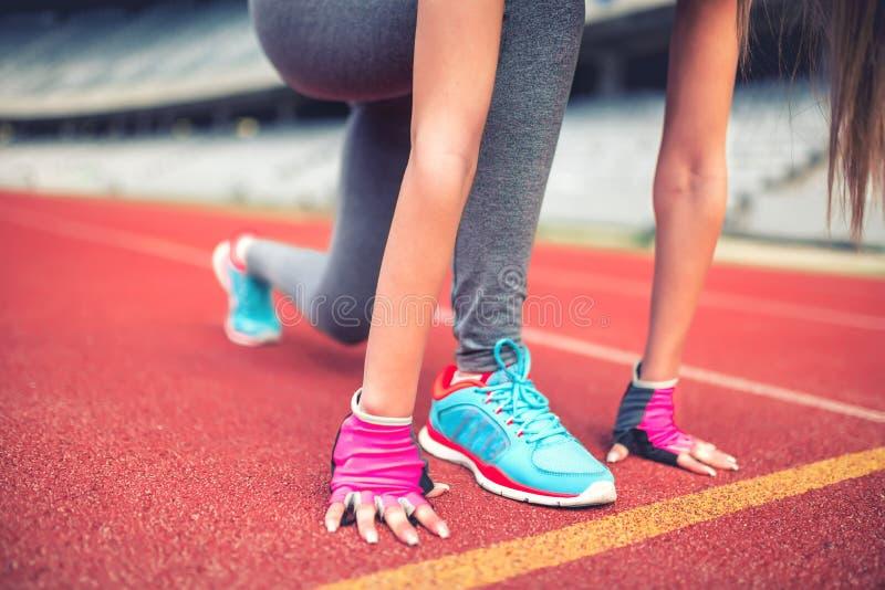 Eignungsathlet auf Startblöcken an der Stadionsbahn, die für einen Sprint sich vorbereitet Eignung, gesundes Lebensstilkonzept stockbild