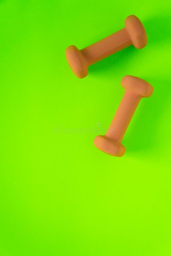Eignungsausrüstung mit den gelb-orangeen Gewichtsdummköpfen der Frauen lokalisiert auf einem Lindgrün mit copyspace Hintergrund m lizenzfreie stockfotografie