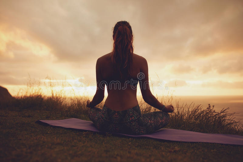 Eignungsfrau in der Lotosyogahaltung während des Sonnenuntergangs stockbild