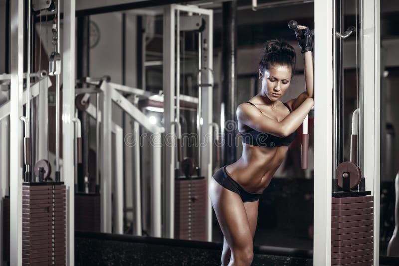 Eignungsfrau in der schwarzen Sportabnutzung mit perfektem Eignungskörper in der Turnhalle lizenzfreies stockbild
