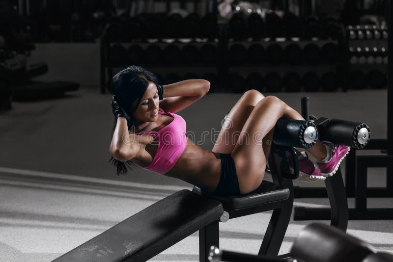 Eignungsfrau in der Sportabnutzung mit perfektem sexy Körper in der Turnhalle stockfotografie