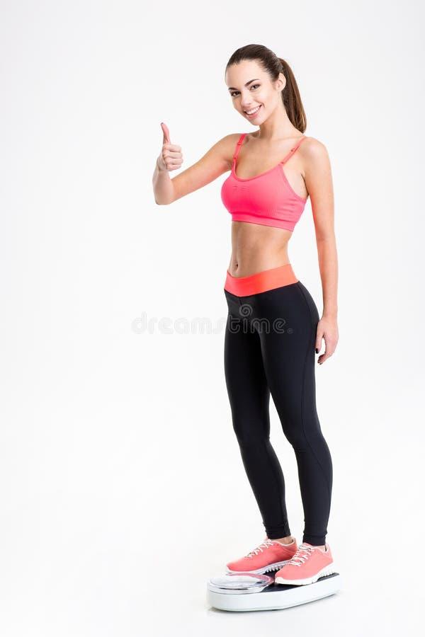Eignungsfrau, die auf wiegender Skala steht und sich Daumen zeigt lizenzfreie stockfotografie