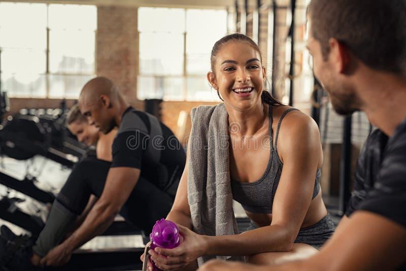 Eignungsfrau, die in der Turnhalle nach Trainingssitzung sich entspannt lizenzfreie stockfotografie