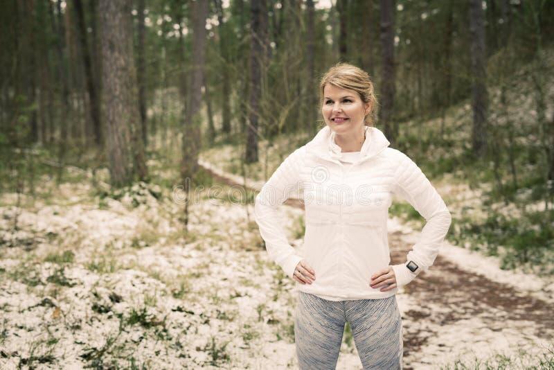Eignungsfrau, die draußen auf der Bahn bereit zu einem Lauf steht lizenzfreies stockbild