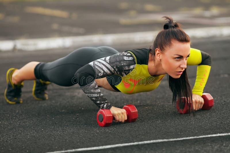 Eignungsfrau, die StoßUPS im Stadion, Quertrainingstraining tut Sportliches Mädchentraining draußen stockfoto